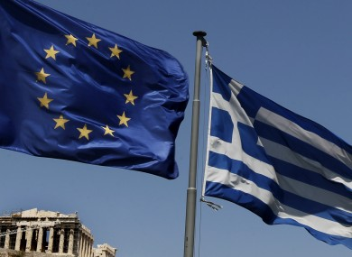 A European Union left and the Greek flag wave above the ancient Parthenon temple, at the Acropolis Hill, in Athens.