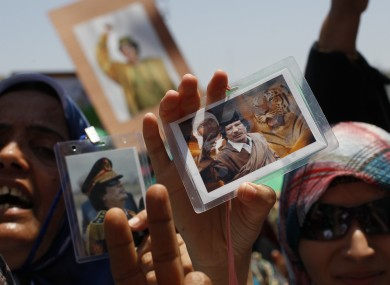 Libyan women show their badges with portraits of Gaddafi during a government-organised media tour in June 2011.