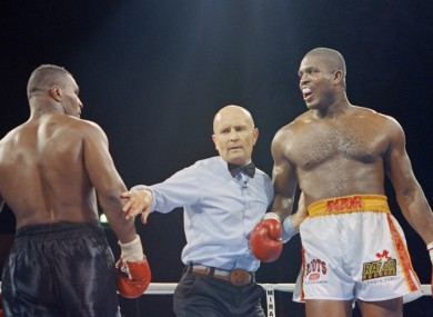 Legendary referee Mills Lane intervenes a mid-round conferring session between Tyson and Ruddock.
