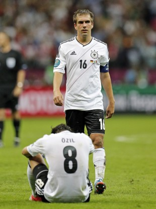 Germany's Mesut Oezil, down, and Philipp Lahm are dejected after the Euro 2012 semi-final.