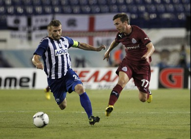 Atromitos' Ioannis Skordas goes for the ball next to Newcastle United's Romain Amalfitano.