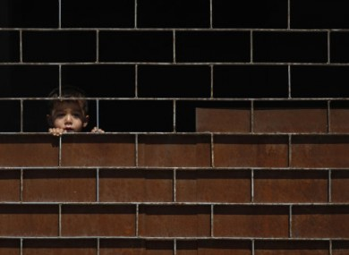 A young Syrian boy watches friends playing at a school where they have sought refuge.