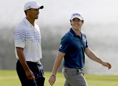 Tiger Woods and Rory McIlroy, of Northern Ireland, walk up the fairway of the 17th hole.