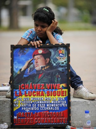 A girl with a poster of Hugo Chavez pictured outside the military academy where his body is lying in state in Caracas