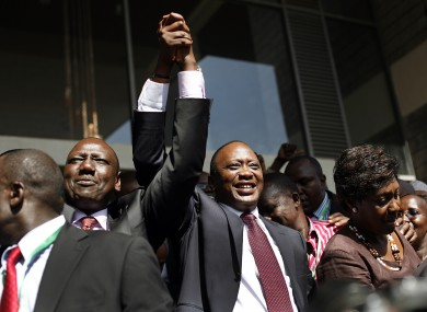Uhuru Kenyatta and his vice-presidential candidate William Ruto wave at supporters after the election result was announced