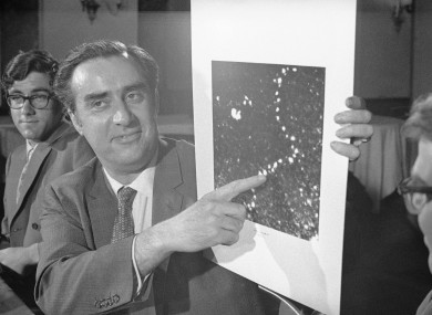 University of Chicago Physics Professor Albert V. Crewe points to a photograph which enables a single atom to be seen within a molecular structure for the first time. Enlarged 5 million times are thorium chains