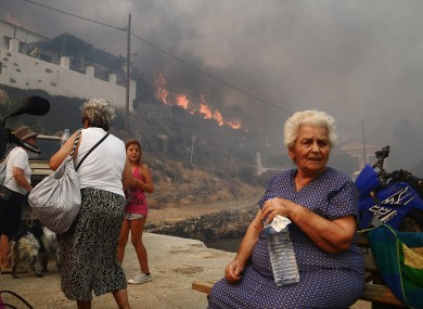 Inhabitants and holidaymakers evacuate the village of Megalo Livadi on Greece's Aegean island of Serifos