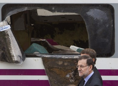 Spanish prime minister Mariano Rajoy walks next to a derailed car at the site of a train accident.