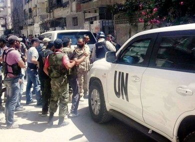 A citizen journalism image provided by the United media office of Arbeen which has been authenticated, showing Syrian rebels escorted the UN investigation team, in Damascus countryside of Zamalka, Syria