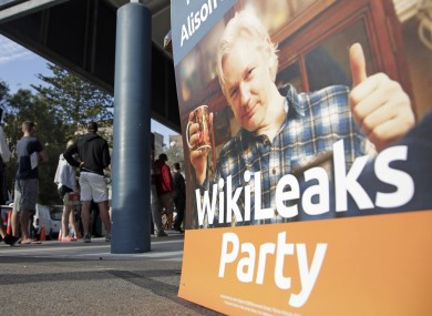 A placard showing WikiLeaks founder Julian Assange is set up as voters line up to fill in their ballots at a polling booth at Bondi Beach in Sydney.