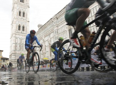 Cyclists ride past the Santa Maria del Fiore Basilica in Florence today.